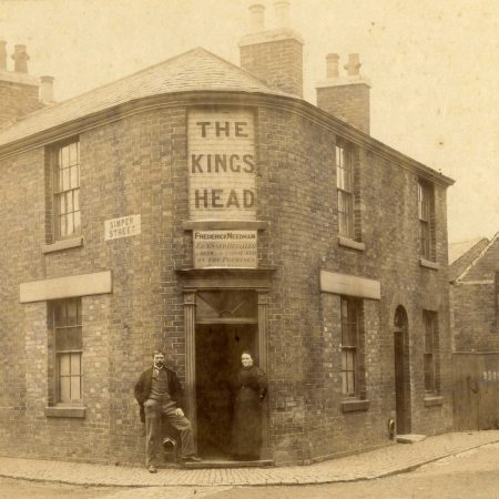 Black and white photograph of The Kings Head, Oakham with pub landlord Frederick Needham and his wide Annie standing outside